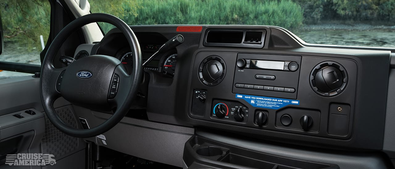 vehicle dashboard showing steering wheel, speedometer, air conditioning controls, vents and radio