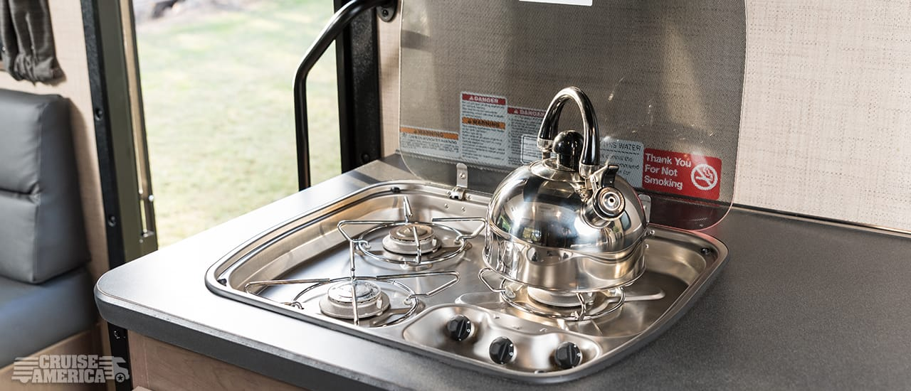 three burner stove top range in open position with tea kettle.